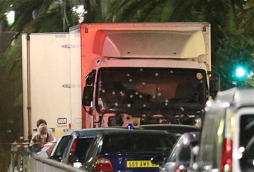 (AP Photo/Luca Bruno). A policeman stands, watching the truck used for the attack near the scene of an attack after a truck drove onto the sidewalk late Thursday, and plowed through a crowd of revelers who gathered to watch the fireworks in the French ...