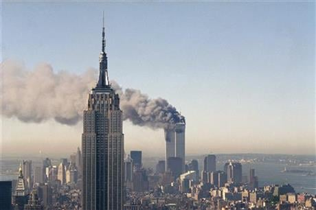 In this Sept. 11, 2001 file photo the twin towers of the World Trade Center burn behind the Empire State Building in New York after terrorists crashed two planes into the towers causing both to collapse.  (AP Photo/Marty Lederhandler)