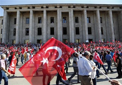 Turkish citizens wave their national flags as they protest against the military coup outside Turkey's parliament near the Turkish military headquarters in Ankara, Turkey.
