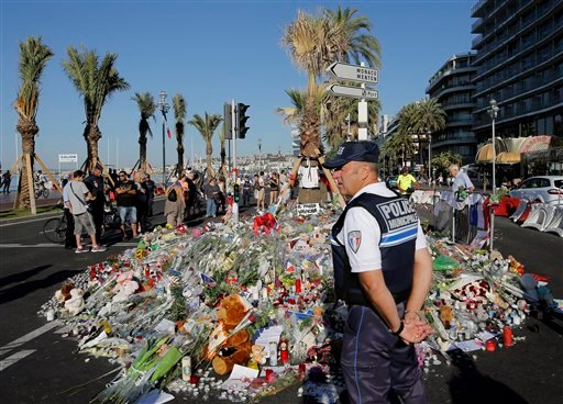 A police officer watches people gathering around a floral tribute for the victims killed during a deadly attack, on the famed Boulevard des Anglais in Nice, southern France, Sunday, July 17, 2016.