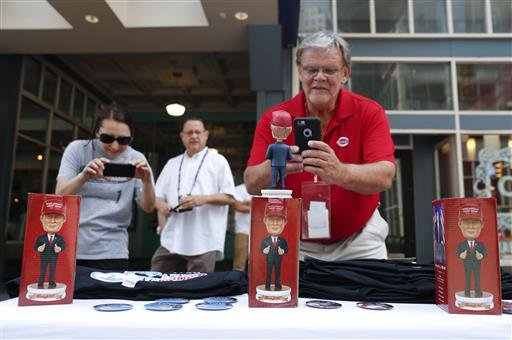 Howard Wilkinson, right, takes a picture of a bobblehead for sale of Republican presidential candidate Donald Trump, Sunday, July 17, 2016, in Cleveland.