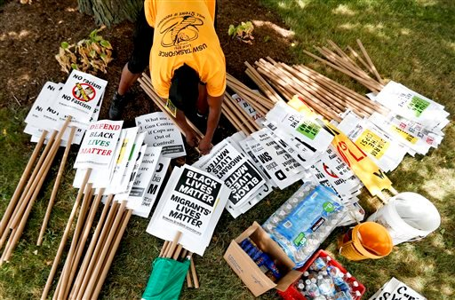 A demonstrator organizes protest signs, Sunday, July 17, 2016, in Cleveland, in preparation for the Republican National Convention that starts Monday.
