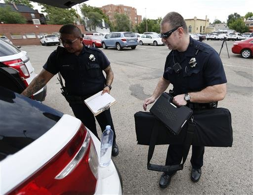 Denver Police Department officers head out to their patrol car after role call for the swing shift in District 6 in downtown Denver. After more than two decades of making officers patrol on their own, the city of Denver has revived two-officer patrols.