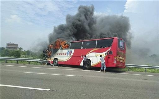 In this photo provided by Yan Cheng, a policeman and another man try to break the windows of a burning tour bus on the side of a highway in Taoyuan, Taiwan, Tuesday, July 19, 2016.