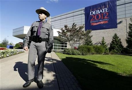 In this Oct. 16, 2012, file photo, New York state trooper Gary DePass stands outside the site of a debate later that day between President Barack Obama and the Republican presidential nominee, former Massachusetts Gov. Mitt Romney, at Hofstra University'