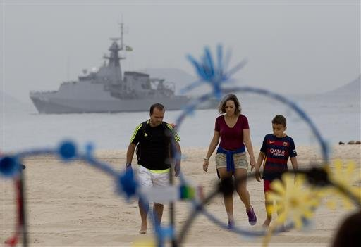A family walks on the shore of Copacabana beach backdropped by a Brazilian navy vessel, in Rio de Janeiro, Brazil, Thursday, July 21, 2016.