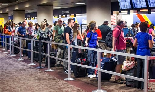 People wait in the Southwest Airlines check-in line at Sky Harbor International Airport, Thursday, July 21, 2016, in Phoenix.