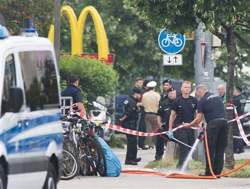 Police stand at a the crime scene where a shooting took place in front of a fast food restaurant leaving multiple people dead the day before on Saturday, July 23, 2016 in Munich, Germany.