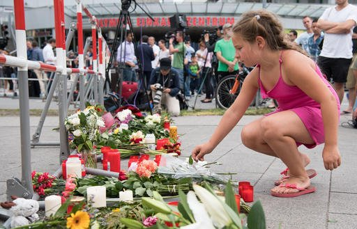 A girl puts down flowers in front of the Olympia shopping center were a shooting took place leaving nine people dead the day before on Saturday, July 23, 2016 in Munich, Germany.