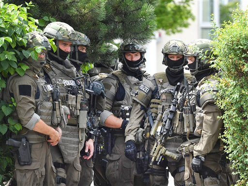 Members of a special forces stand near a fast food restaurant where a shooting took place leaving nine people dead the day before on Saturday, July 23, 2016 in Munich, Germany.