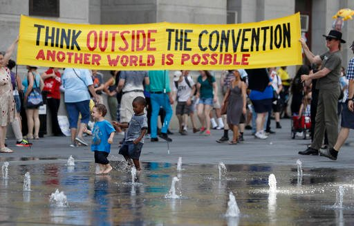 Demonstrators carry a sign around Dillworth Park as two youngsters play in the fountain on Sunday, July 24, 2016, in Philadelphia.