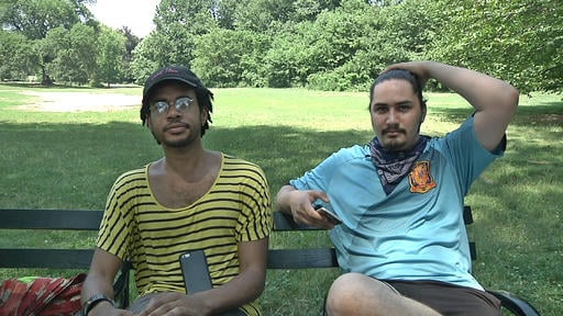 "In this July 13, 2016 frame grab from video, Jordan Clark, left, and Lewis Gutierrez sit in Prospect Park as they talk about their new ""Pokemon Go"" business in the Brooklyn."