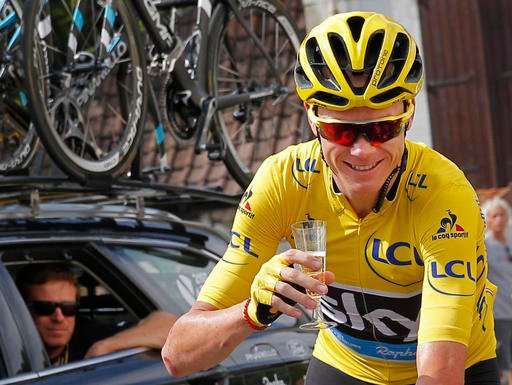Britain's Chris Froome, wearing the overall leader's yellow jersey, celebrates with a glass of champagne during the twenty-first stage of the Tour de France.