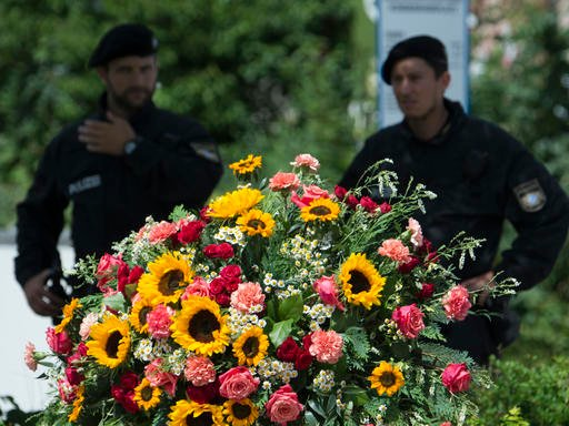 Police officers stand behind a wreath near the Olympia shopping center