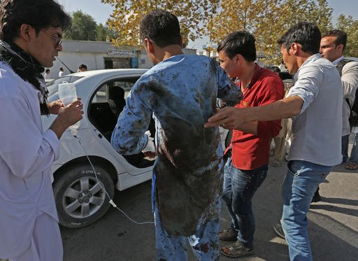 Afghans help a man who was injured in a deadly explosion that struck a protest march by ethnic Hazaras, in Kabul, Afghanistan, Saturday, July 23, 2016.