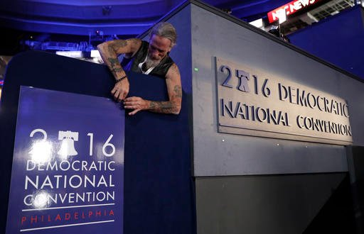 Gary Gort, a set carpenter with CNN, adjusts a sign during preparations before the 2016 Democratic Convention, Sunday, July 24, 2016, in Philadelphia. (AP Photo/John Locher)