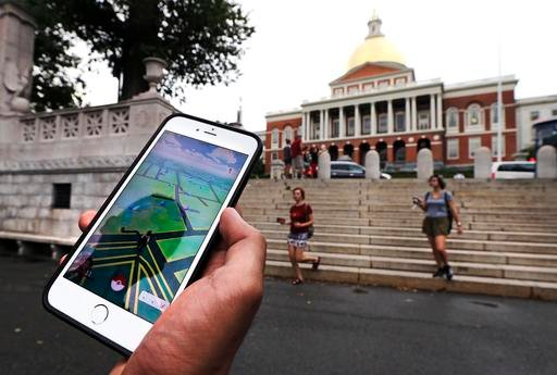 """In this Monday, July 18, 2016, photo, a """"Pokemon Go"""" player shows his mobile phone while walking through the Boston Common, outside the Massachusetts Statehouse in Boston. Historical markers dot the landscape of old cities, barely noticed by passers-by. T"""