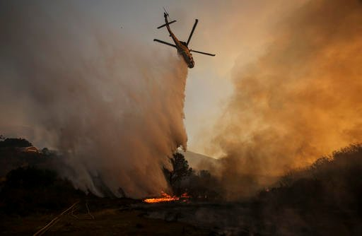 A helicopter maks a drop on a wildfire near Placenta Caynon Road in Santa Clarita, Calif., Sunday, July 24, 2016. Thousands of homes remained evacuated Sunday as two massive wildfires raged in tinder-dry California hills and canyons. (AP Photo/Ringo H.W.