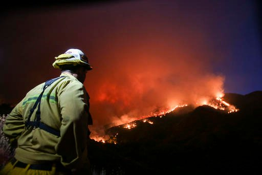 A firefighter watches a wildfire near Placenta Canyon Road in Santa Clarita, Calif., Sunday, July 24, 2016. Thousands of homes remained evacuated Sunday as two massive wildfires raged in tinder-dry California hills and canyons. (AP Photo/Ringo H.W. Chiu)