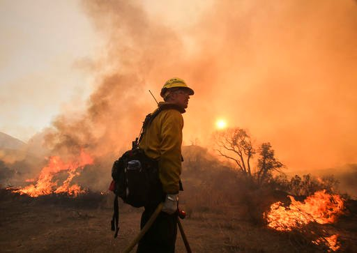 "A firefighter watches a wildfire near Placenta Caynon Road in Santa Clarita, Calif., Sunday, July 24, 2016. Flames raced down a steep hillside ""like a freight train,"" leaving smoldering remains of homes and forcing thousands to flee the wildfire churning"