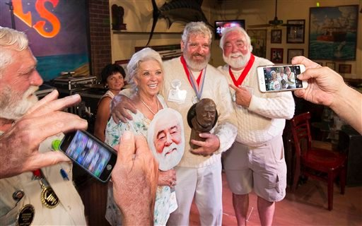 """In this Saturday, July 23, 2016 photo provided by the Florida Keys News Bureau, Dave Hemingway, center, poses for smartphone photos with celebrity chef Paula Deen, left, and her husband Michael Groover, right, after Dave Hemingway won the 2016 Ernest """"Pap"""