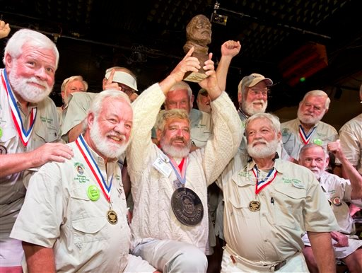 "In this Saturday, July 23, 2016, photo provided by the Florida Keys News Bureau, Dave Hemingway, center, hoists his trophy after winning the 2016 Ernest ""Papa"" Hemingway Look-Alike Contest at Sloppy Joe's Bar in Key West, Fla. Success for Dave Hemingway c"