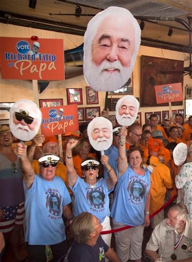 """In this Saturday, July 23, 2016, photo provided by the Florida Keys News Bureau, supporters of Michael Groover and Richard Filip cheer for their favorites at the 2016 Ernest """"Papa"""" Hemingway Look-Alike Contest at Sloppy Joe's Bar in Key West, Fla. The eve"""