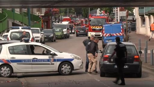 In this grab made from video, police officers speak to a driver as they close off a road during a hostage situation in Normandy, France, Tuesday, July 26, 2016. Two attackers seized hostages in a church near the Normandy city of Rouen on Tuesday, killing