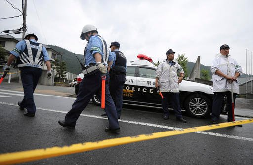 Police officers stand guard at the main gate of Tsukui Yamayuri-en, a facility for the disabled where a number of people were killed and dozens injured in a knife attack in Sagamihara, outside Tokyo Tuesday, July 26, 2016. Police said they responded to a