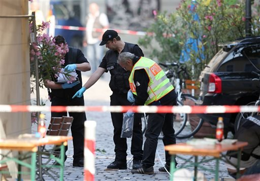 German police investigates at the site in Ansbach, Germany, Monday, July 25, 2016, where a failed asylum-seeker from Syria blew himself up and wounded people after being turned away from an open-air music festival in southern Germany. The man recorded a c