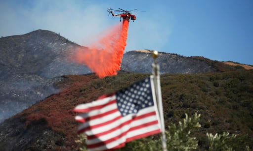 Framed by a burned-over hillside, rear, and an American flag in the foreground, a helicopter drops fire retardant ahead of advancing flames as a wildfire approaches Placerita Canyon in Santa Clarita, Calif., Monday, July 25, 2016. A raging wildfire that f