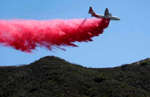 A plane drops fire retardant on an unburned ridge in advance of flames as a wildfire fire burns in Placerita Canyon in Santa Clarita, Calif., Monday, July 25, 2016. A raging wildfire that forced thousands from their homes on the edge of Los Angeles contin