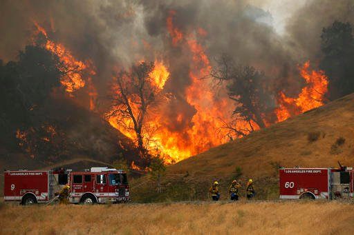 A hillside erupts in flame as a wildfire burns in Placerita Canyon in Santa Clarita, Calif., Monday, July 25, 2016. A raging wildfire that forced thousands from their homes on the edge of Los Angeles continued to burn out of control Monday as frustrated f