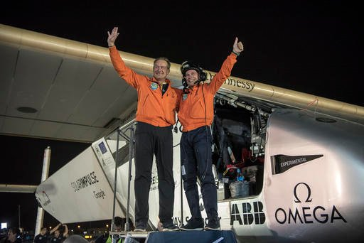 In this July 26, 2016 photo provided by Solar Impulse, pilots Bertrand Piccard, right, and Andre Borschberg celebrate the landing of their plane at an airport in Abu Dhabi, United Arab Emirates, early Tuesday, July 26, 2016. The world's first round-the-wo