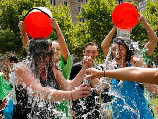 In this Aug. 7, 2014, file photo, two women get doused during the ice bucket challenge at Boston's Copley Square to raise funds and awareness for ALS.