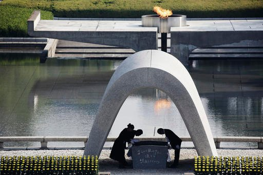 In this Aug. 6, 2015 file photo, Kazumi Matsui, right, mayor of Hiroshima, and the family of the deceased bow before they place the victims list of the Atomic Bomb at Hiroshima Memorial Cenotaph.