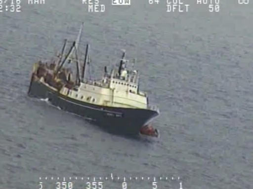 In this Tuesday, July 26, 2016 frame from video provided by the U.S. Coast Guard, crew from a sinking fishing boat, left, board life rafts off Alaska's Aleutian Islands in the Bering Sea. When the Alaska Juris started taking on water Tuesday, crew members