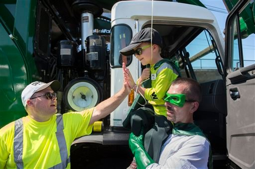 Six-year-old Ethan Dean, who was diagnosed with cystic fibrosis at two weeks old, gets a high five while carried by Capt. Recycle, Mitch Zak during his stop at The Sacramento Bee to pick up recycling as part of his Make-A-Wish Foundation activity on Tuesd