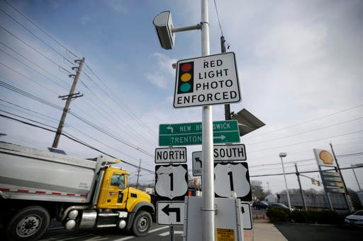 In this Dec. 16, 2014, file photo, a truck passes a red light photo enforcement sign that is placed below a red light camera at the intersection of Route 1 and Franklin Corner Road in Lawrence Township, N.J.