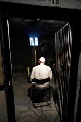 Pope Francis prays in the underground prison cell of a Catholic saint, Maximilian Kolbe, at the former Nazi German death camp of Auschwitz in Oswiecim, Poland, Friday, July 29, 2016. Kolbe, a Polish Catholic friar, sacrificed his own life during the war t