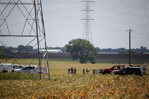 Investigators surround the scene in a field near Lockhart, Texas where a hot air balloon carrying at least 16 people collided with power lines Saturday.