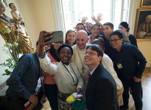 Pope Francis poses for a selfie with youths after he had lunch with them at the Bishop's residence in Krakow, Poland, Saturday.