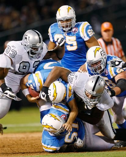 Oakland Raiders defensive end Richard Seymour (92) sacks San Diego Chargers quarterback Philip Rivers (17) during the second quarter of an NFL football game Monday, Sept. 14, 2009, in Oakland, Calif. Looking on are Raiders defensive end Tommy Kelly (93),