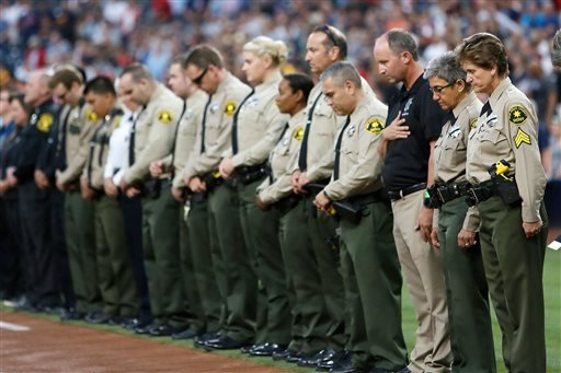 San Diego County Sheriff's Department officers stand in memory of officer Jonathan DeGuzman with a moment of silence before a baseball game between the Cincinnati Reds and the San Diego Padres on Friday, July 29, 2016, in San Diego. DeGuzman was fatally s