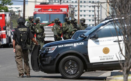 San Diego Police SWAT officers surround a house with a possible suspect inside Friday, July 29, 2016, in San Diego. One San Diego police officer was killed and another was wounded in a shootout following a late-night traffic stop, Friday night. A suspect
