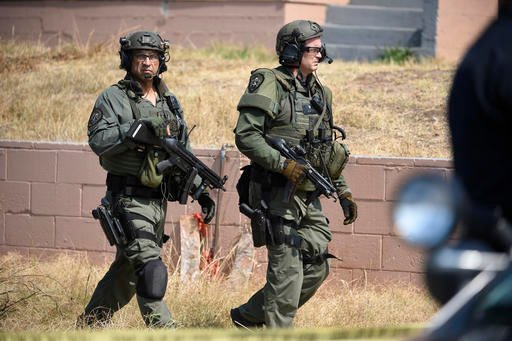 San Diego Police SWAT officers walk around to the back side of a house with a possible suspect inside Friday, July 29, 2016 in San Diego. One San Diego police officer was killed and another was wounded in a shootout following a late-night traffic stop, Fr