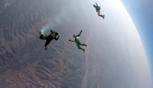 In this image made from a video provided by Mondelez International, Luke Aikins, center, skydives without a parachute over Simi Valley, Calif., Saturday, July 30, 2016. After a two-minute freefall, Aikins landed dead center in the 100-by-100-foot net at t
