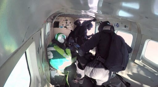 In this image made from a video provided by Mondelez International Luke Aikins, left, prepares to go skydiving without a parachute over Simi Valley, Calif., Saturday, July 30, 2016. After a two-minute freefall, Aikins landed dead center in the 100-by-100-