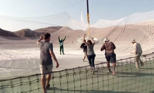 In this image made from a video provided by Mondelez International, Luke Aikins, second from left, celebrates after skydiving without a parachute in Simi Valley, Calif., Saturday, July 30, 2016. After a two-minute freefall, Aikins landed in the 100-by-100