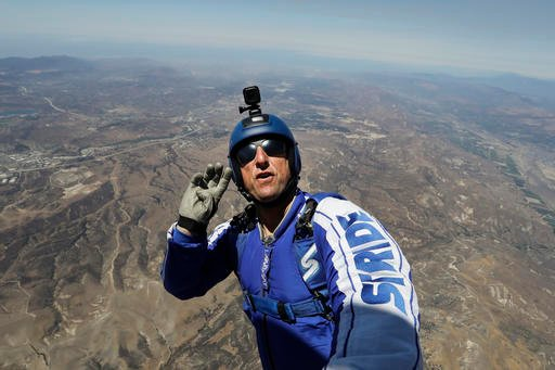 In this Monday, July 25, 2016 photo, skydiver Luke Aikins signals to pilot Aaron Fitzgerald as he prepares to jump from a helicopter in Simi Valley, Calif. After months of training, this elite skydiver says he's ready to leave his chute in the plane when